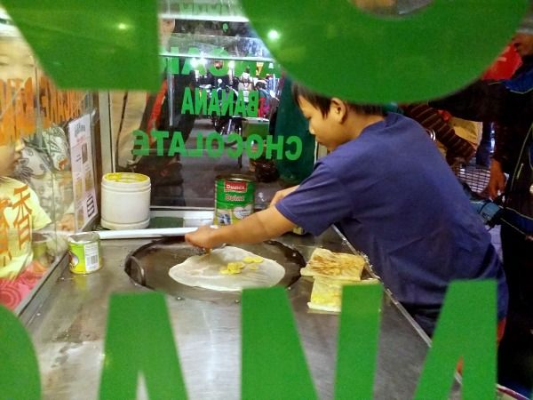 young boy making banana pancakes in pub street