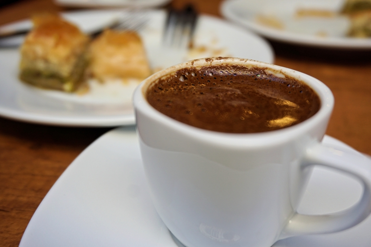 turkish coffee in a white cup served with baklava